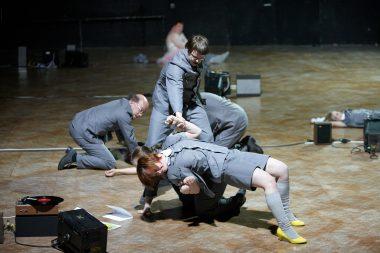 Drei Menschen in grauen Kostümen rangeln auf dem Boden