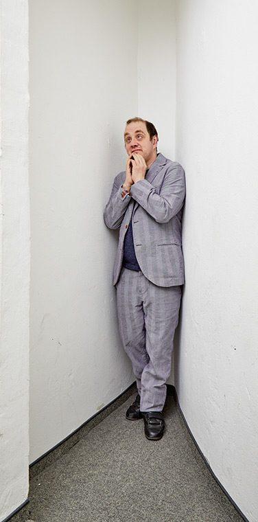 Dennis Seidel steht mit einem Anzug bekleidet in einer Ecke. Er hebt beide Hände an sein Kinn und schaut nach oben.